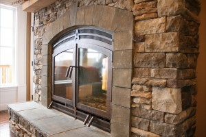Indoor-Outdoor See-Throughh Fireplace with Masonry Finish and Bronze Doors