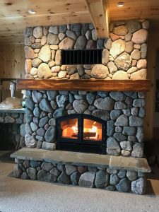 high tech wood burning fireplace in home with stone masonry finish
