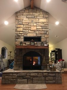 high tech see through wood burning fireplace in home with stone finish