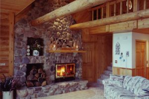 masonry wood burning fireplace in log cabin living room