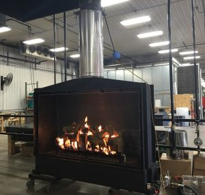 large open gas fireplace with log set being tested