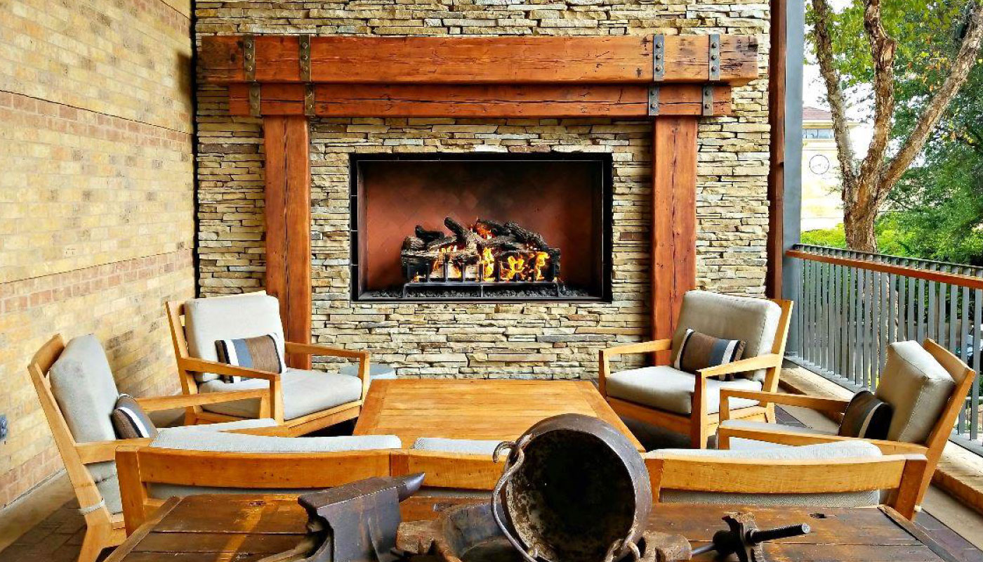 outdoor gas fireplace with logs on patio
