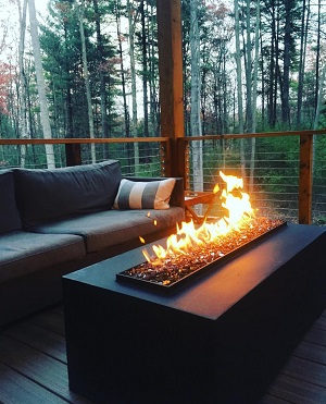custom outdoor fire table with no glass on deck of private residence