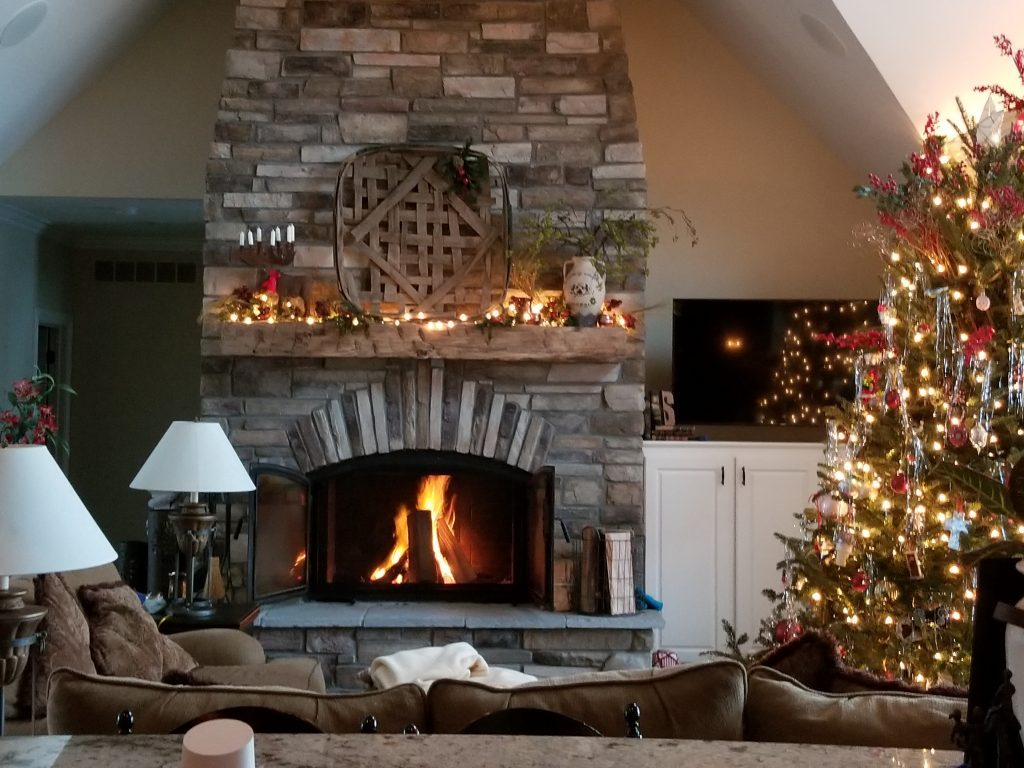 acucraft wood burning fireplace with open doors during christmas in a living room