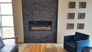 linear single sided hospitality gas fireplace with dark surround in surgery waiting area
