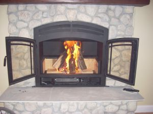 wood burning fireplace with open doors
