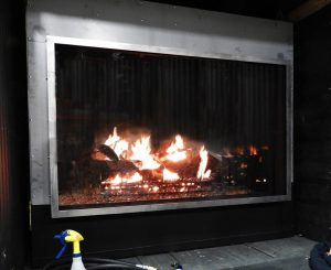 see through gas fireplace with logs being tested