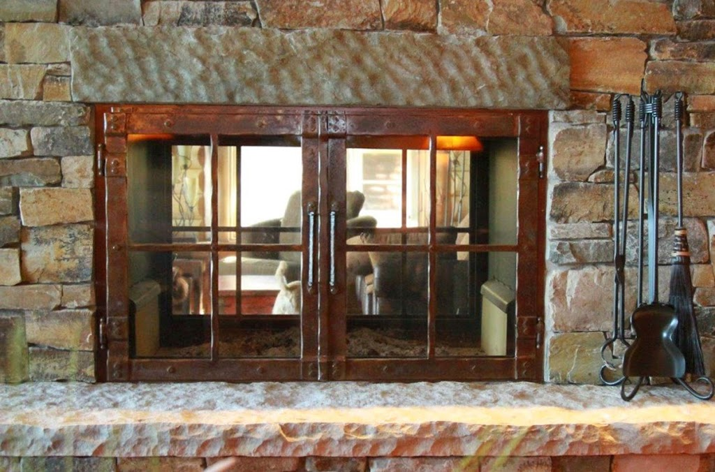 Wood-Burning See-Through Fireplace Design with Hammered Patina Doors