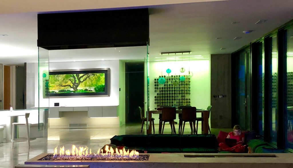 acucraft custom four sided indoor gas fire pit with open viewing area and suspended glass and hood in sunken living room
