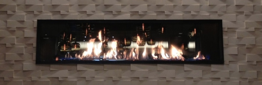 acucraft linear gas fireplace with reflective panels in hotel bar