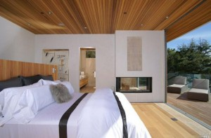 see through gas fireplace in modern bedroom