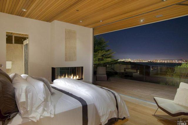 see through gas fireplace between bedroom and bathroom overlooking san Francisco bay