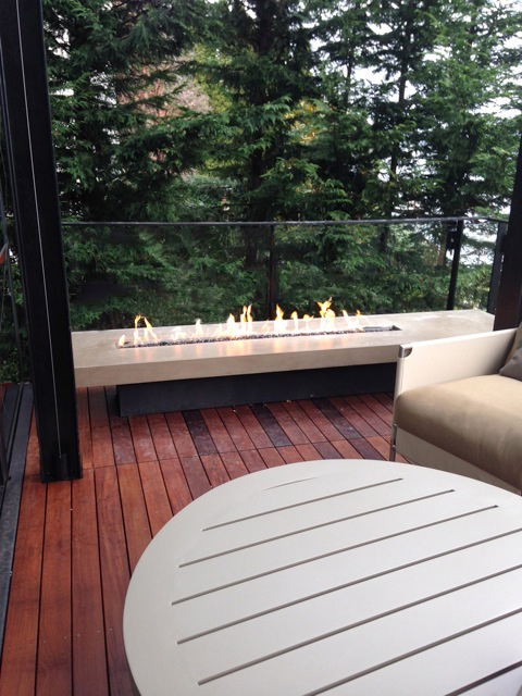 outdoor linear glass fireplace on deck of private residence