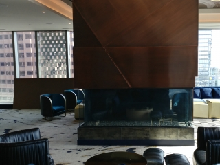 panoramic 3 sided gas fireplace in modern hotel lounge