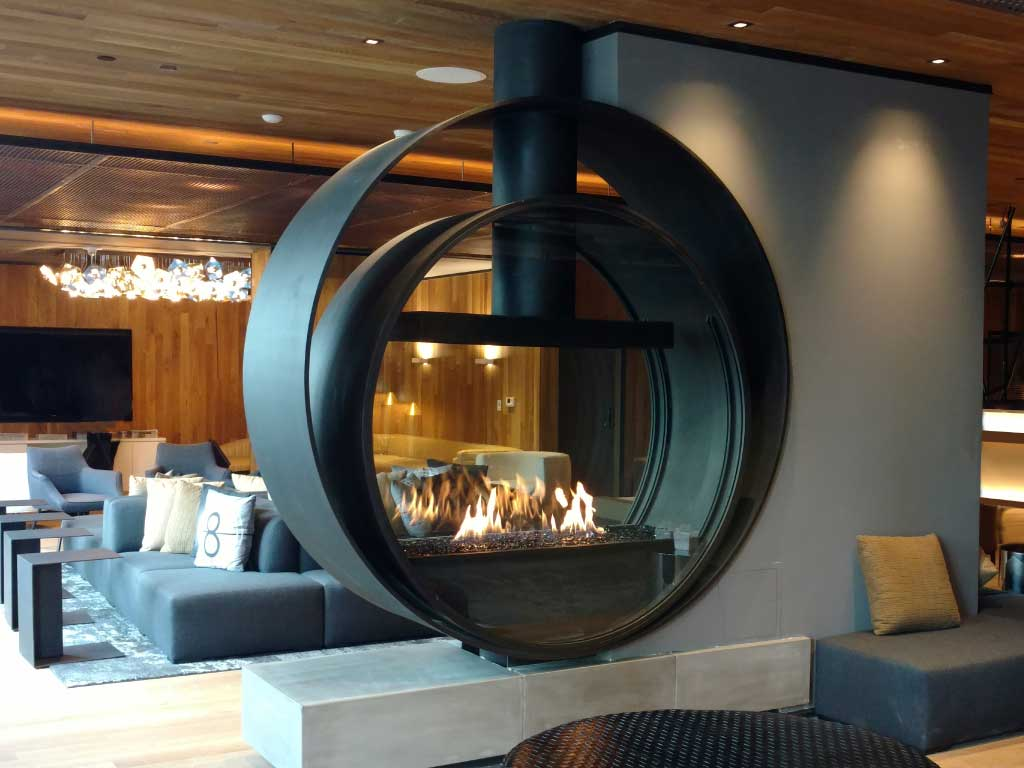 custom upright circular gas fireplace in hotel lobby