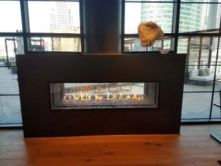 see-through linear gas fireplace with exposed flue