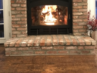 indoor outdoor see through wood burning fireplace with brick surround and tv