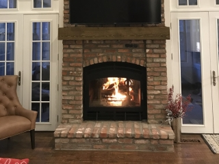 indoor outdoor see through wood burning fireplace with single door and brick surround with tv
