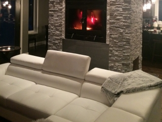 see through wood burning fireplace with rectangular front and doors and white rock surround