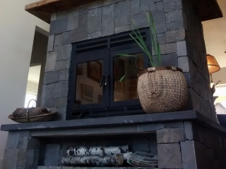 see through wood burning fireplace with rectangular front and doors and stone surround