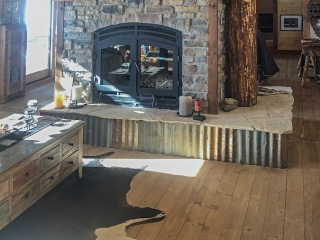 see through wood burning fireplace in cabin with exposed flue