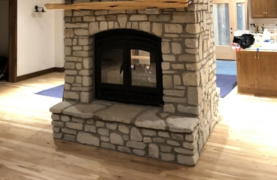 see through wood burning fireplace with white stone surround and wood mantel
