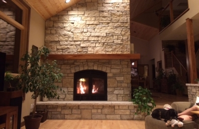 see through wood burning fireplace with light stone surround and hearth with wood mantel