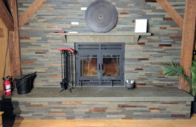 single sided wood burning fireplace with modern surround and wood beams