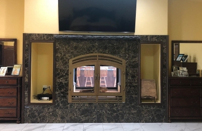 see through wood burning fireplace with marble surround in modern bedroom