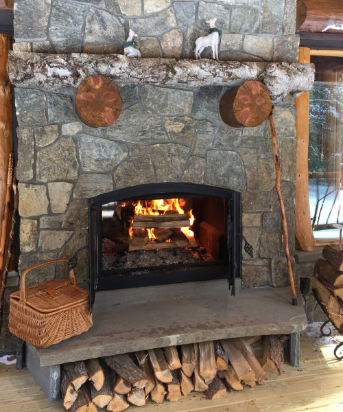 see through indoor outdoor wood burning fireplace with open doors