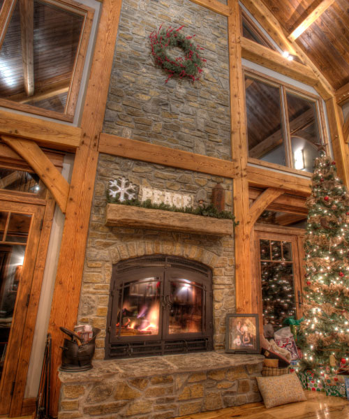 see through indoor outdoor wood fireplace with christmas tree
