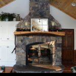 single sided wood burning fireplace with stone surround in living room