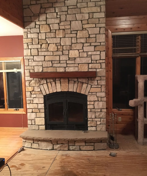 single sided wood burning fireplace with light stone surround