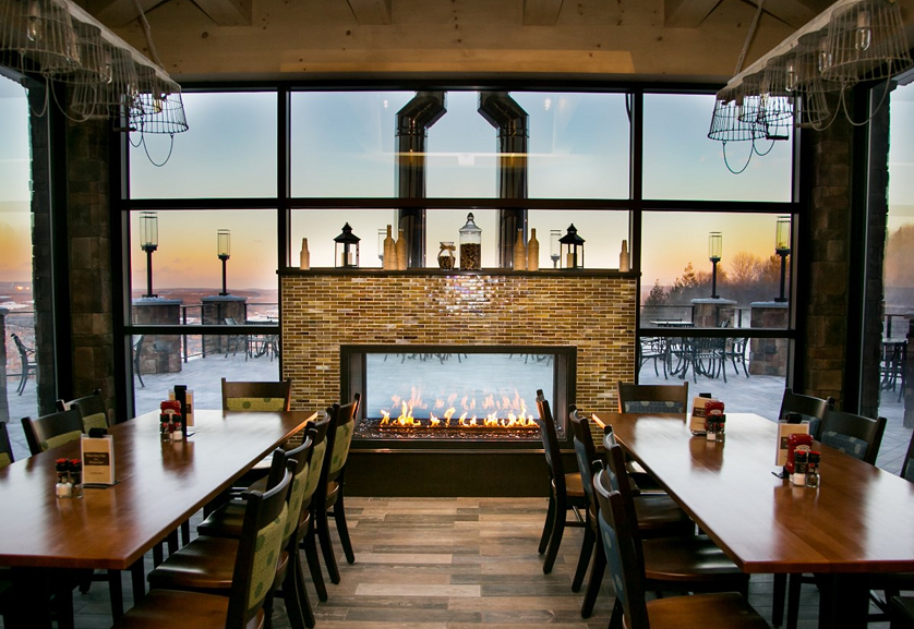 indoor outdoor see through gas fireplace in ski resort pub and grill with sunset