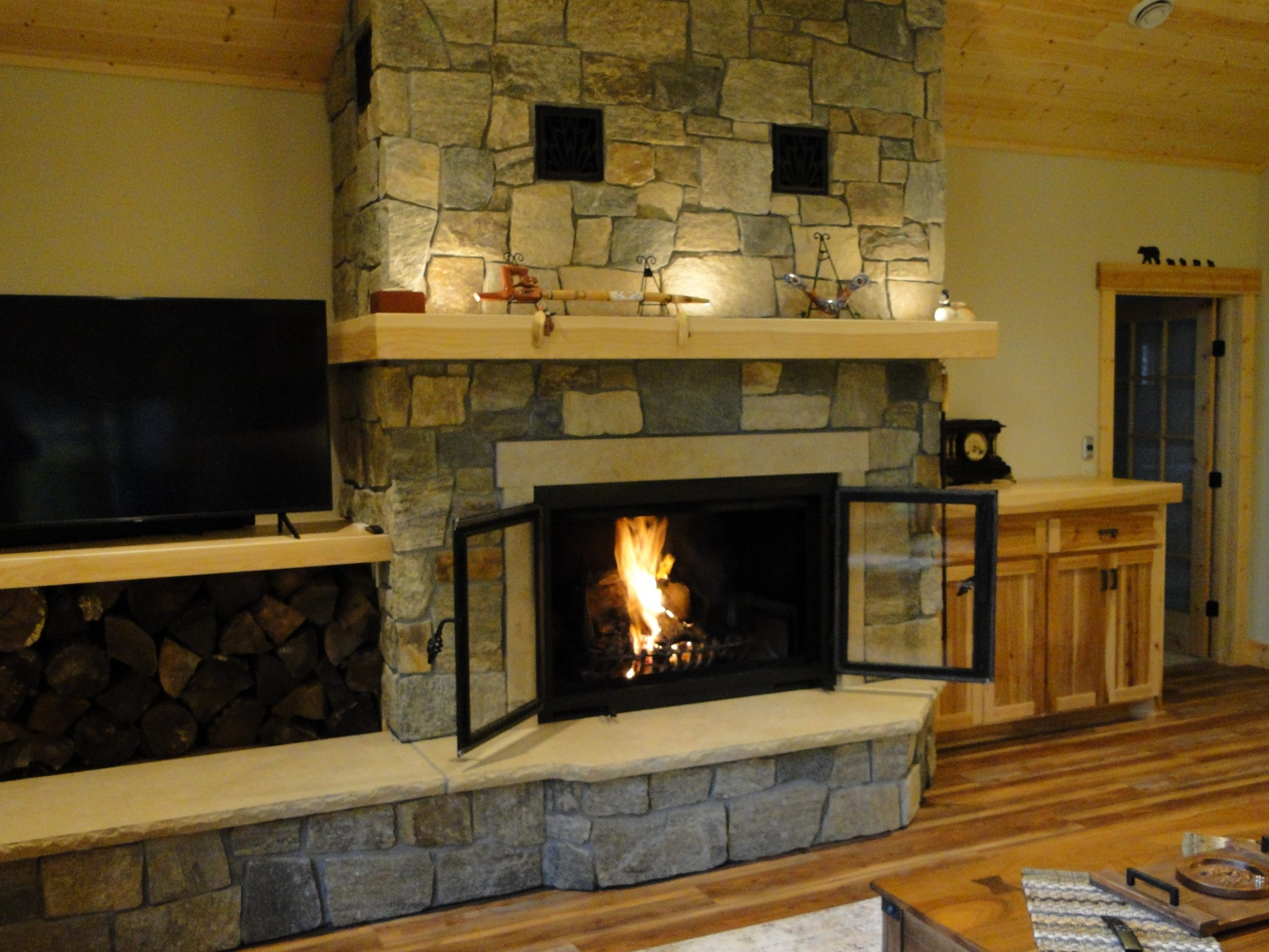 A single sided wood burning fireplace with open rectangle front doors