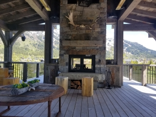 indoor outdoor see through wood burning fireplace with mountain view