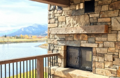 indoor outdoor see through wood burning fireplace with stone finish and mountain lake view