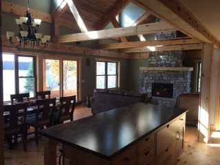 single sided wood burning fireplace with stone surround in cabin living room