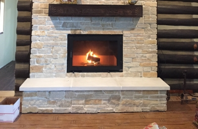 modern wood burning fireplace in living room with light stone surround