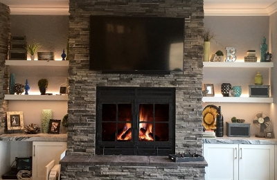 single sided wood burning fireplace with grids and dark gray surround in modern living room