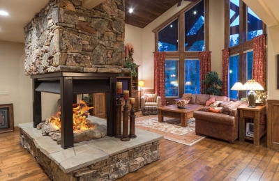 four sided open gas fireplace with logs in rustic living room