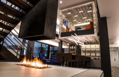 four sided open gas fireplace with suspended hood in corporate office