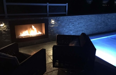 outdoor open gas fireplace next to a pool