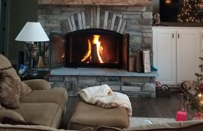 single sided wood burning fireplace with double doors and stone surround