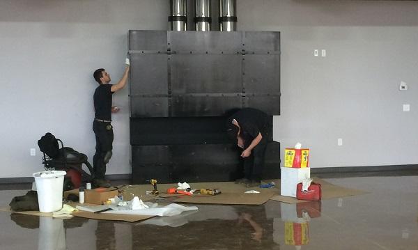 Fireplace technicians servicing a fireplace