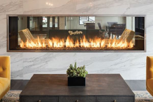 see through gas linear fireplace in apartment lobby