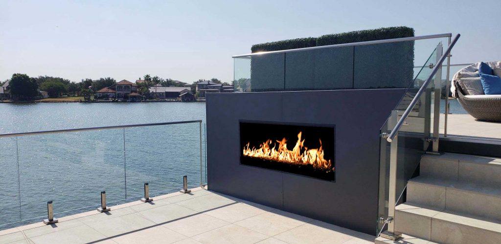 outdoor open gas fireplace with firescreen