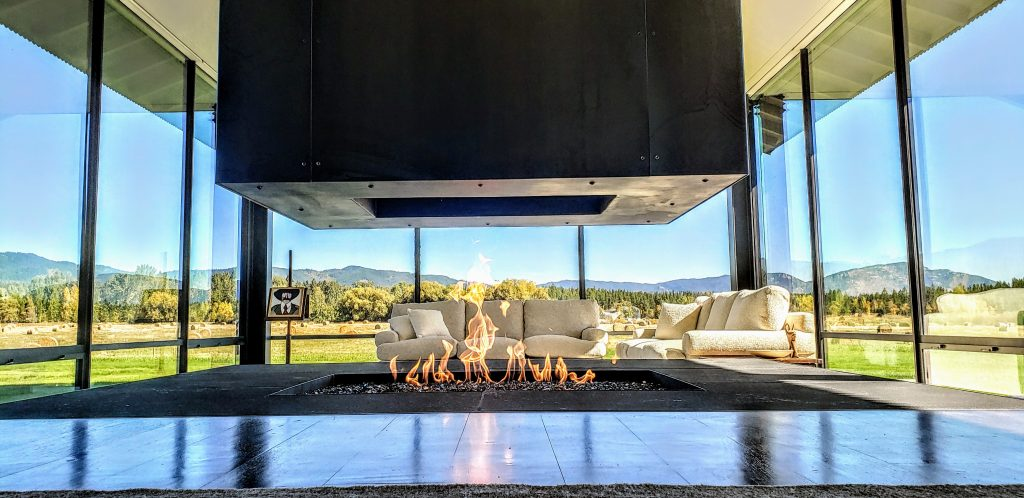 "four sided open gas fireplace with 20"" flames in modern Montana home"