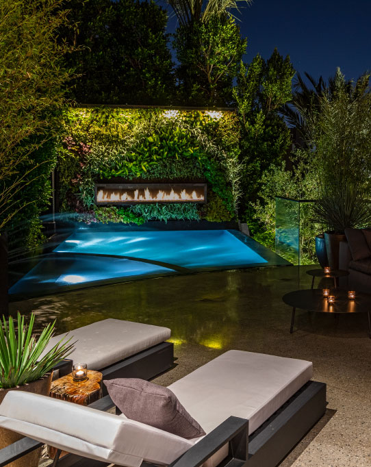 Linear fireplace in a plant wall overlooking a pool