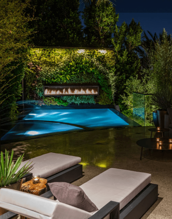 Lounge chairs overlooking a pool surrounded by greenery at night